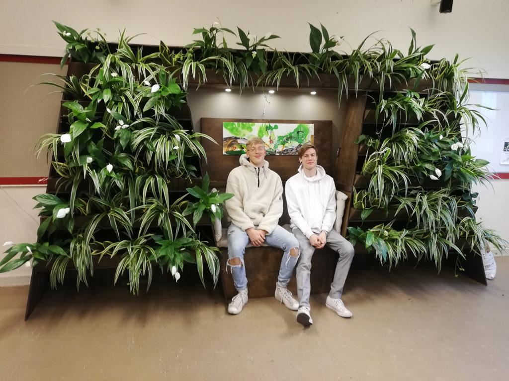 En växtställning med gröna växter på båda sidor om, och ovanför, en bänk. På bänken sitter två killar.