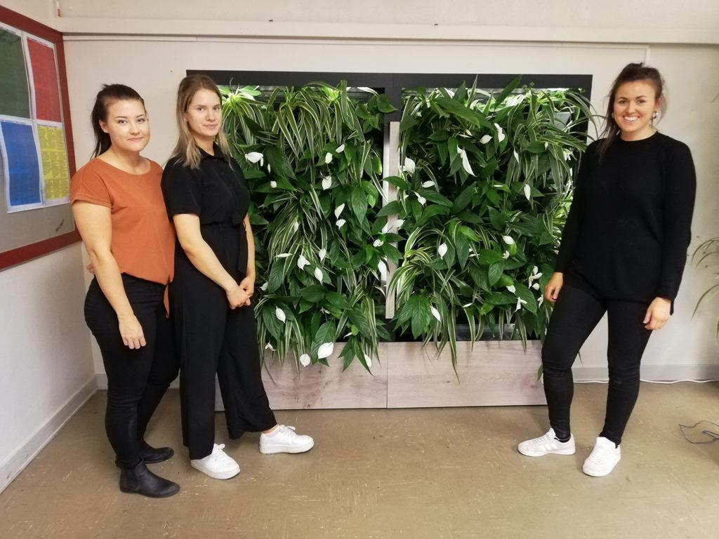 Tre tjejer som står bredvid en ställning med gröna växter.