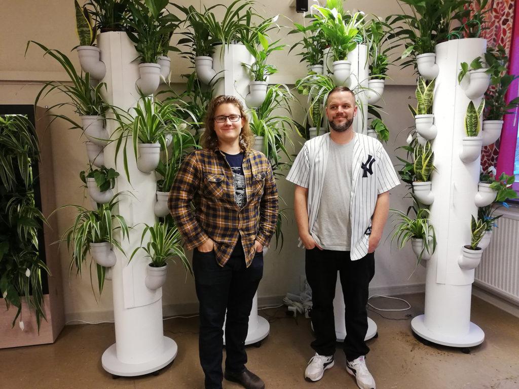 En tjej och en kille som står vid fyra pelare med gröna växter..