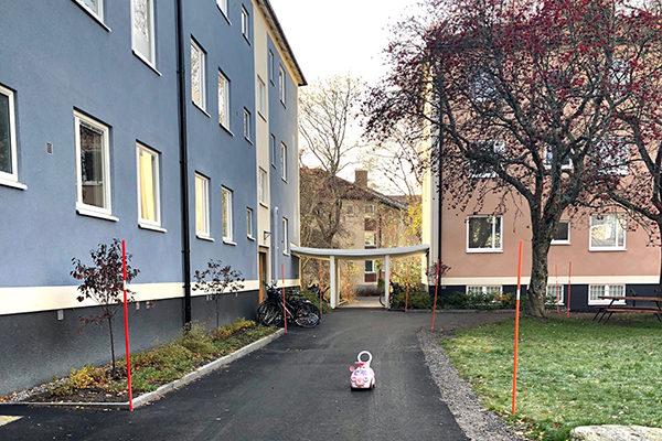 Foto på två lägenhetshus. På gångvägen utanför står en leksaksbil för barn.