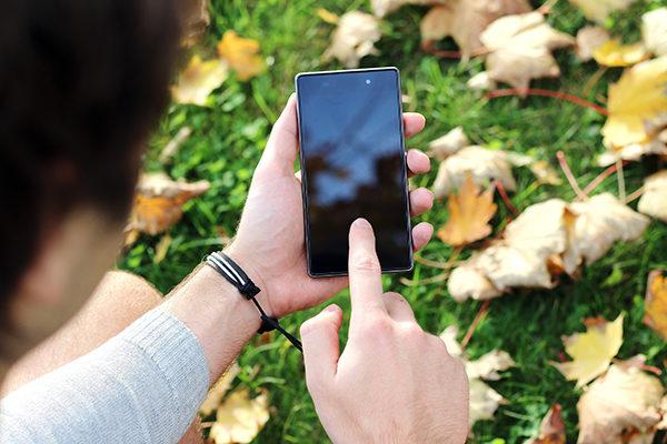 Person som trycker på en mobil i utomhusmiljö