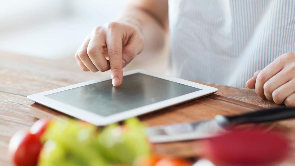 Person som tittar på en surfplatta i köket. Frukt i förgrunden på köksbänken.