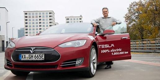 En man som står vid sin vinröda bil, elbilen Tesla.