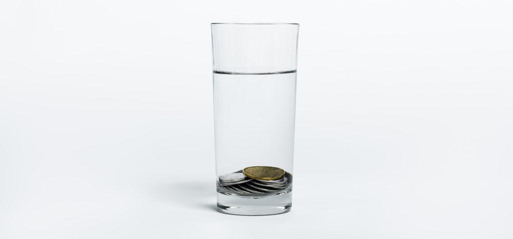 Ett glas med vatten, med mynt i botten av glaset.