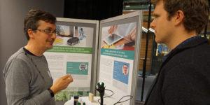 Björn Hedin och Nelson Sommerfeldt diskuterar vid affisch för projektet Design av digital teknik för att stötta energirelaterade beteendeförändringar i köket.