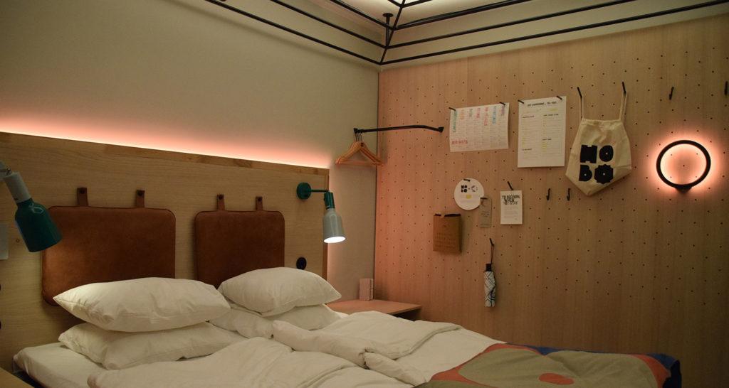 Hotellrum med två sängar och belysning bakom sänggaveln och i taket.