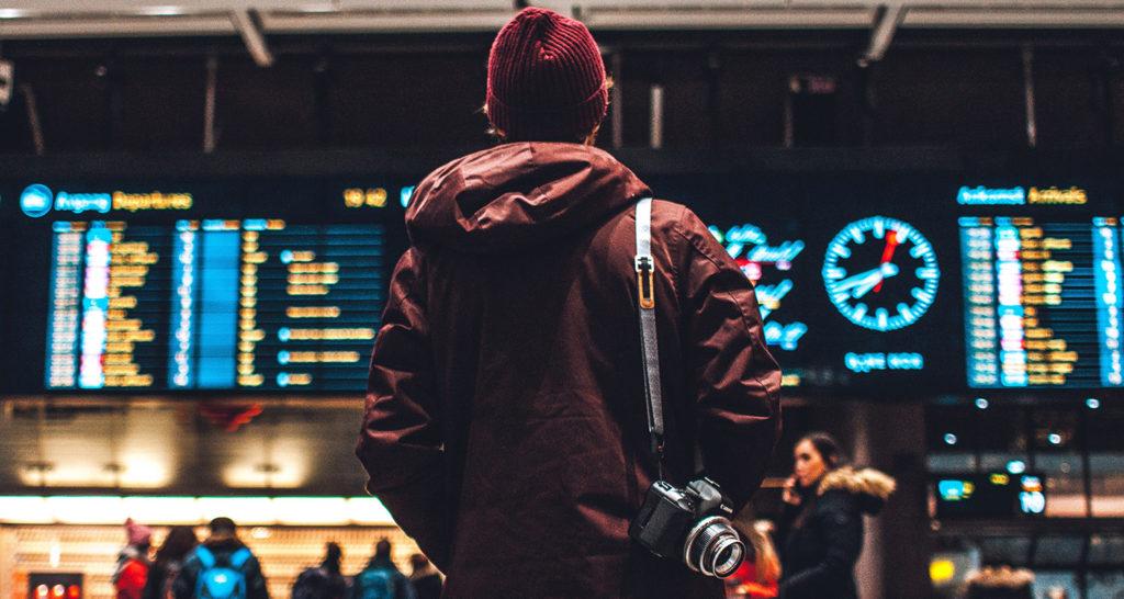 Person som står i en vänthall och tittar på avgångstider på en digital tavla på väggen.
