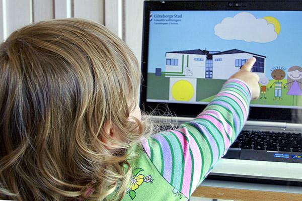 Ett barn som pekar på en datorskärm med ett hus som har solceller på taket.