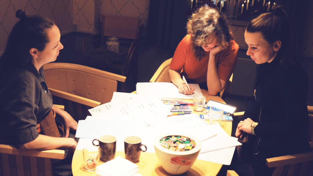 Tre kvinnor som sitter runt ett bord och diskuterar.