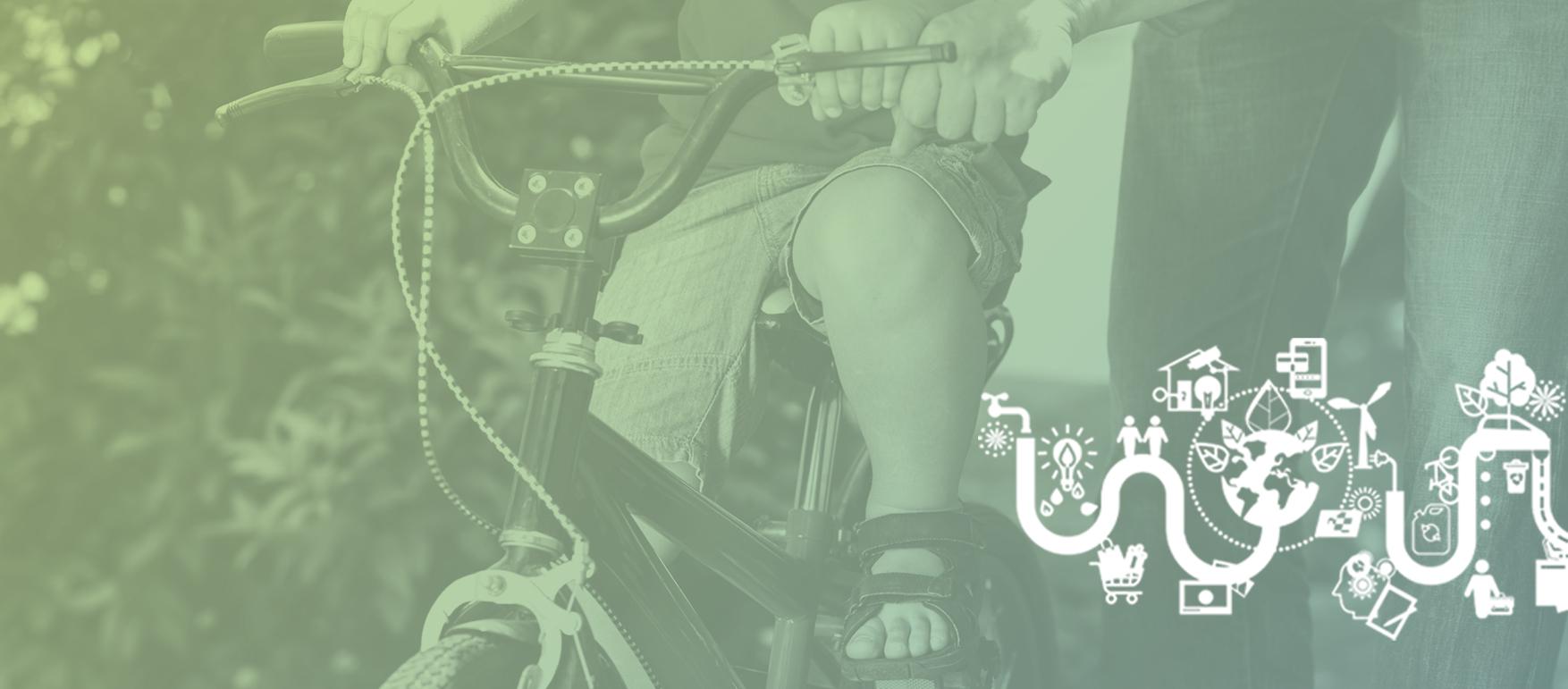 Pojke som cyklar och en förälder hjälper till att hålla i styret.