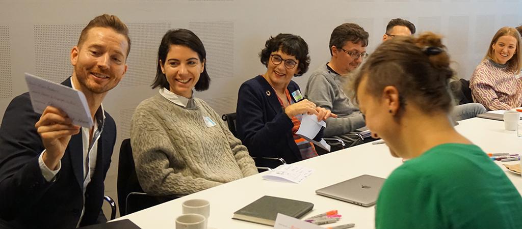 Personer som sitter och diskuterar vid ett bord och skrattar.