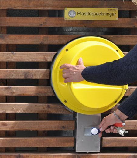 Bild utomhus på ett sopnedkast och en person som håller på att öppna sopluckan.