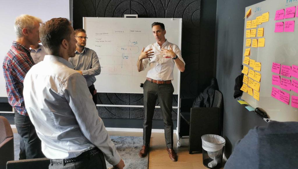 Bild inomhus på personer som står och diskuterar vid en tavla med post it-lappar på.