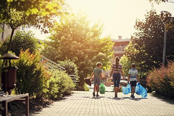 Tre barn som promenerar utomhus för att slänga återvinning.