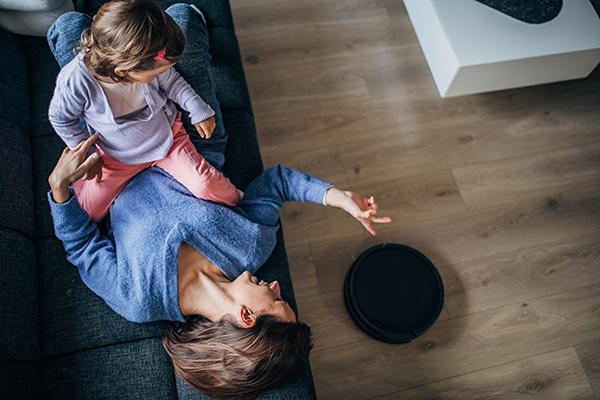 En mamma ligger på soffan hemma med sin dotter, medan en robotdammsugare gör rent på golvet.