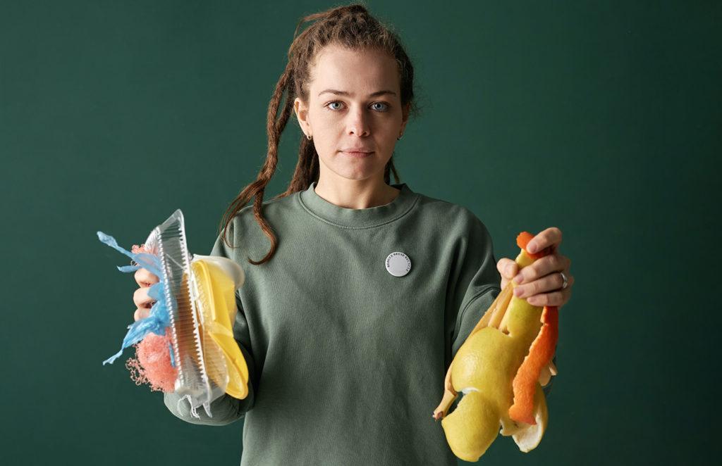 Tjej som håller plaståtervinning i ena handen och skal från frukt i den andra handen.